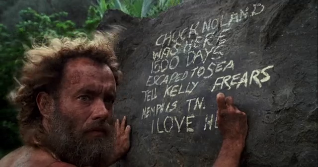 A bearded Tom Hanks carves a message into a rock while stranded on an island in Cast Away