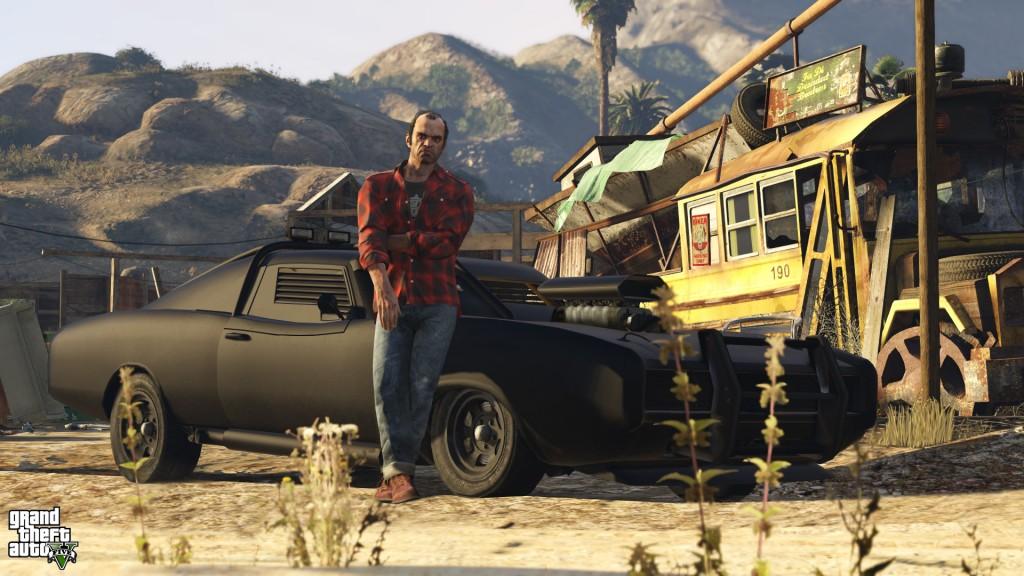Trevor from GTA V leans against a car in the desert.