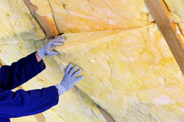 gloved person handling insulation