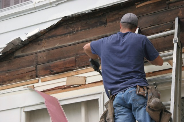 man on ladder fixes home's siding