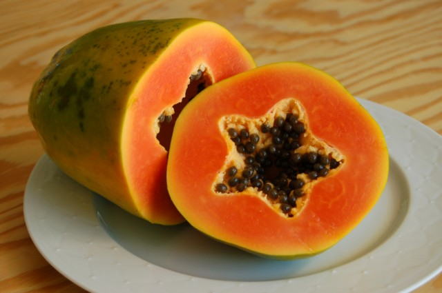 papaya cut in half on a white plate