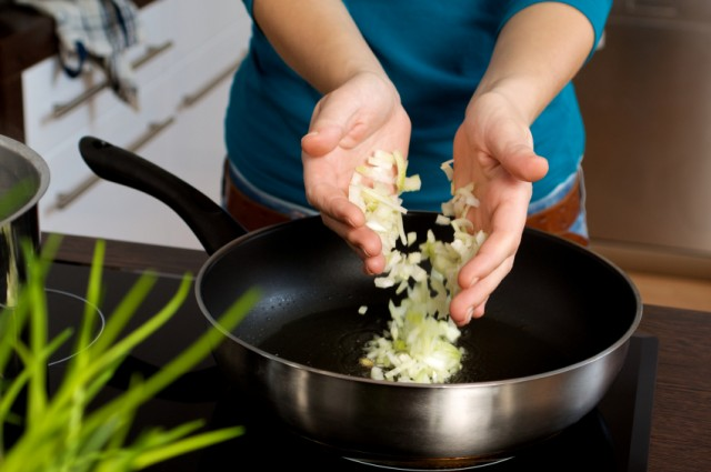 Woman cooking onions in a skillet