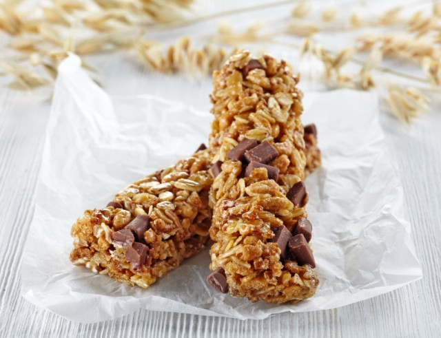 two homemade granola bars with chocolate chips on parchment paper