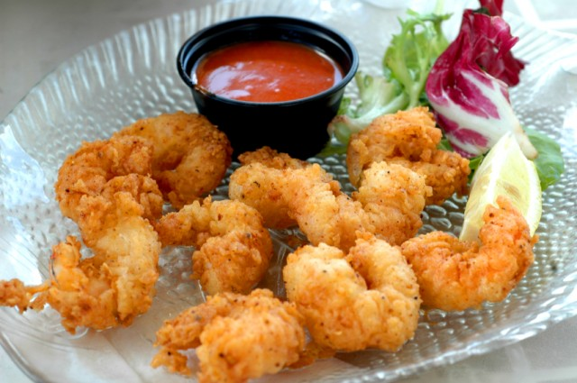 popcorn shrimp on a plate with hot sauce