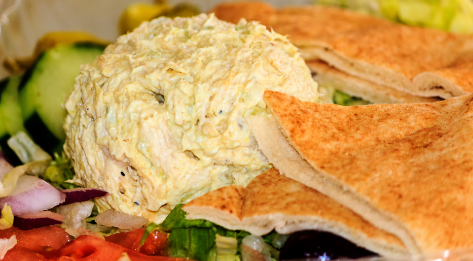 glob of chicken salad on top of vegetables with pita bread