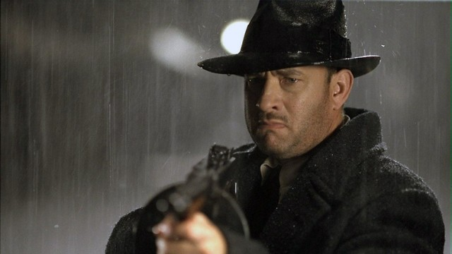 Tom Hanks holds up a shotgun while standing in the rain in a coat and fedora in Road to Perdition