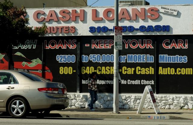 A woman walks past a firm offering cash