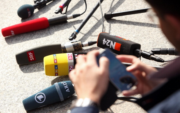 A broadcast reporter searches for his microphone