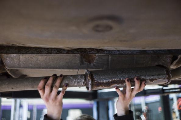 A mechanic repairs a car