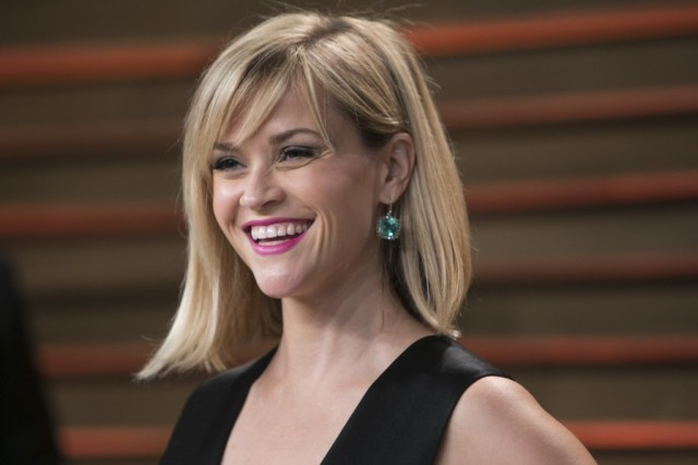 Reese Witherspoon smiling at photographers while posing for photos in a black dress.