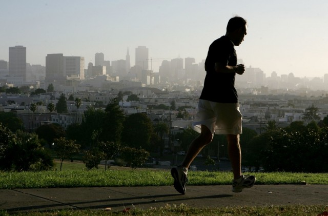SAN FRANCISCO - JULY 13: With the San Francisco skyline in the background, a jogger runs through Dolores Park July 13, 2005 in San Francisco. Runner's World Magazine has just named San Francisco the best city for running in the United States based on its weather, the number of running clubs, racing events and the the ample park space available for runners. (Photo by Justin Sullivan/Getty Images)