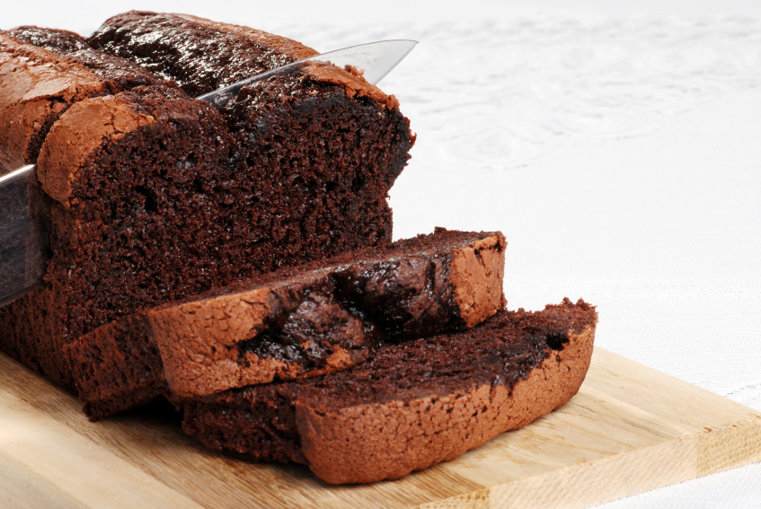 slicing a piece of rich, chocolate pound cake