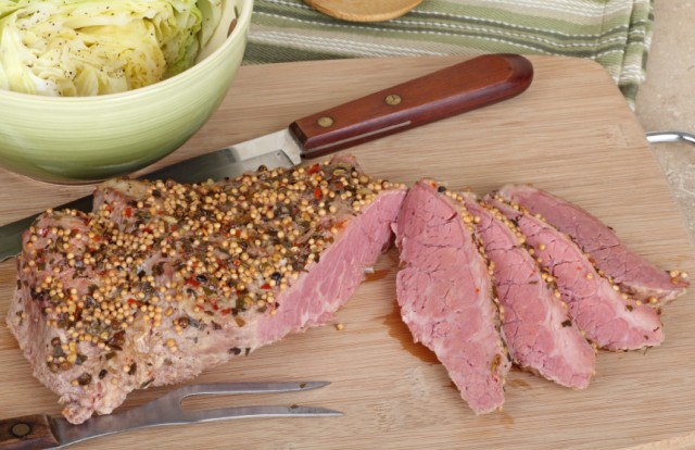 Sliced corned beef with cabbage on a cutting board