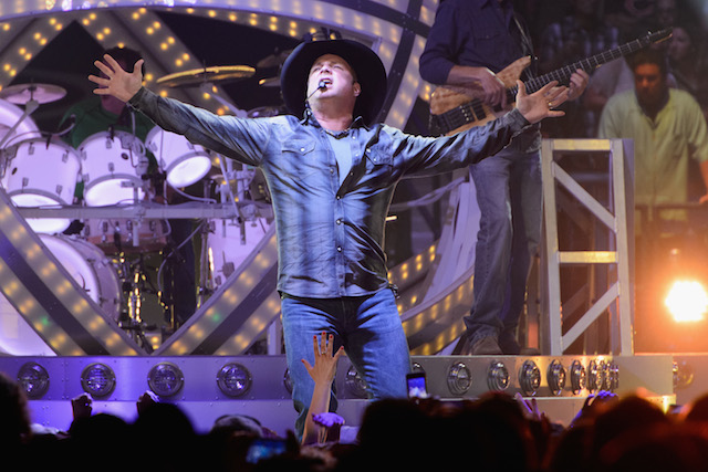 Garth Brooks has his arms spread out as he performs on stage.