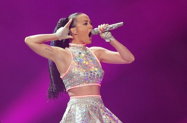 Katy Perry holds a microphone while performing in a sequined outfit behind a purple screen.