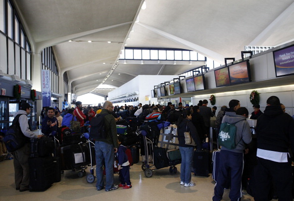 A group of people wait on line at Newark Liberty International Airport.