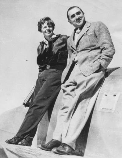 Amelia Earhart and Paul Mantz pose on an airplane.