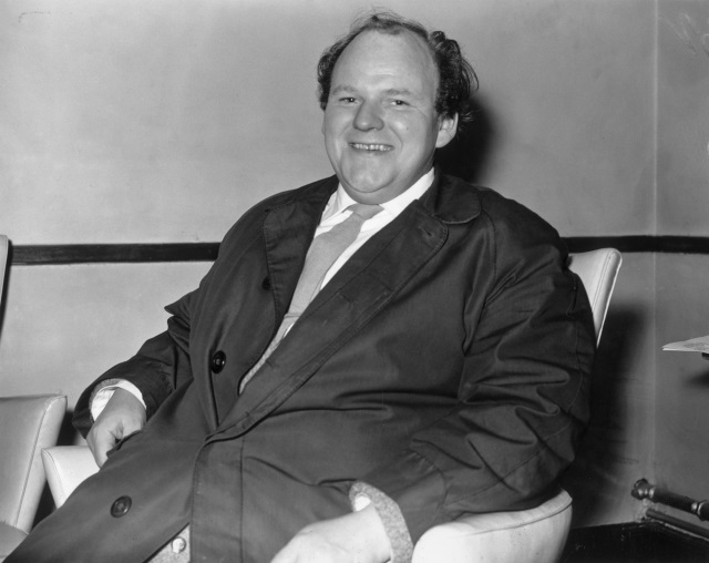 Roy Kinnear sitting on a chair laughing