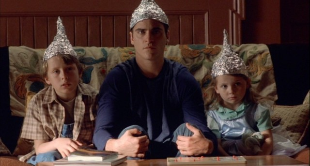 Joaquin Phoenix sits next to two kids on a couch in foil hats in a scene from Signs