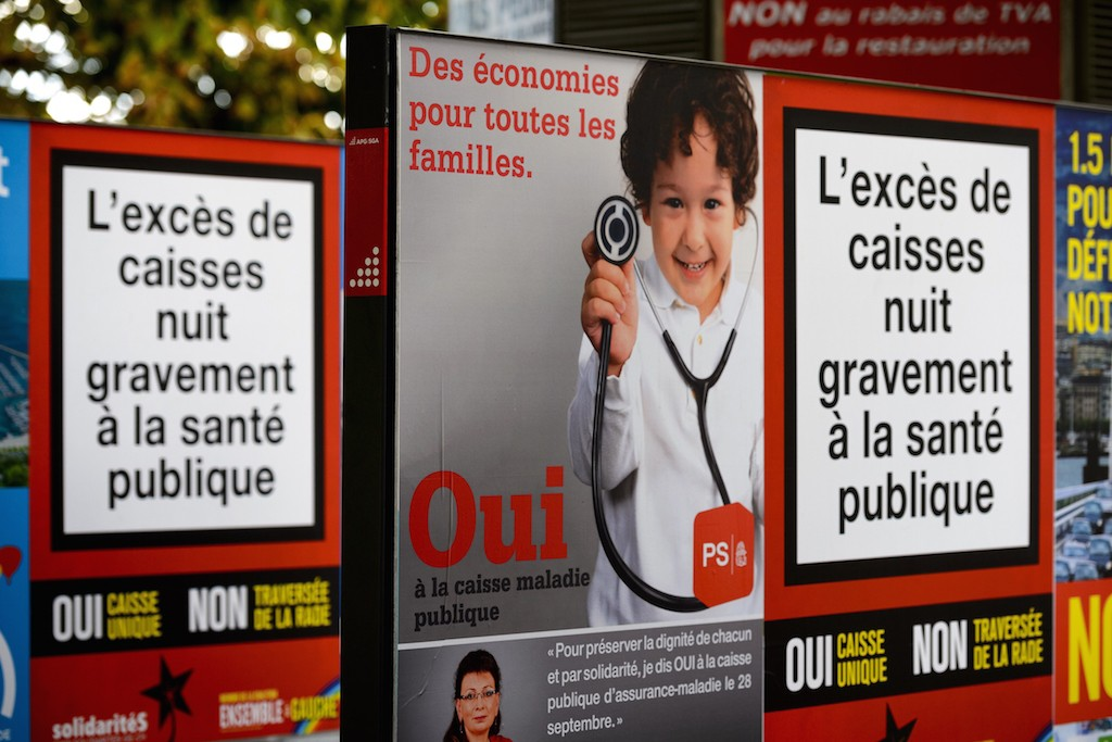 Campaign posters promoting a single health insurance public system are seen on September 21, 2014 in Geneva. The Swiss will head to the polls on September 28, 2014 to vote on whether or not they want to do away with a system often hailed abroad as efficient but a source of growing frustration at home, amid soaring healthcare costs. Photo by Fabrice Coffrini/AFP/Getty Images.