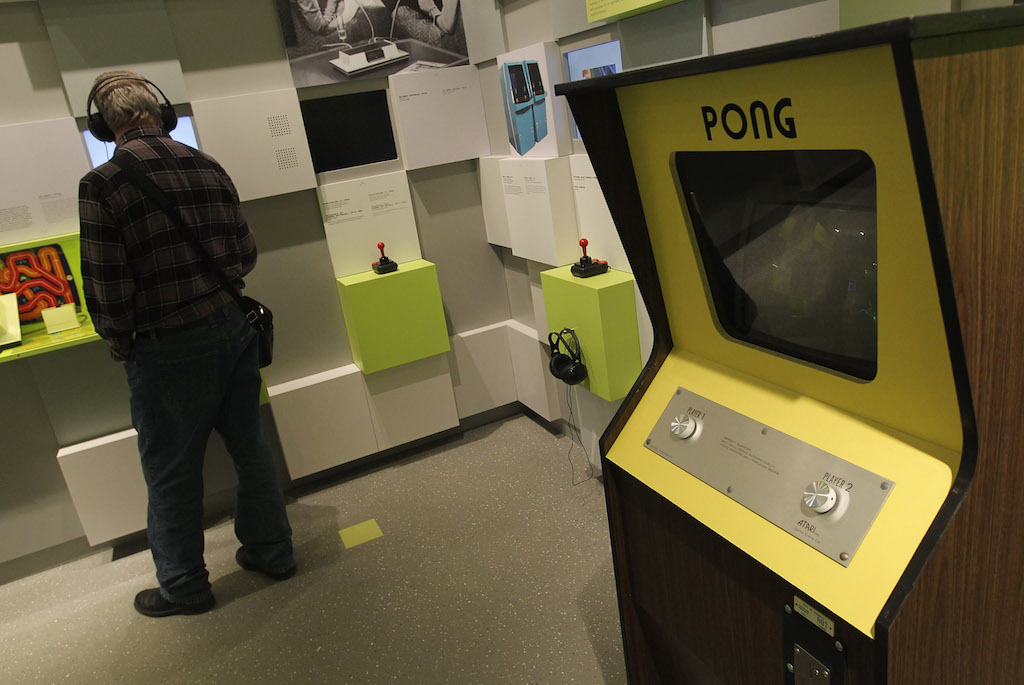 A visitor listens to an audio presentation next to a standing console of Pong, one of the earliest, commercially successful video games, at the Computer Game Museum (Computerspielemuseum) on January 26, 2011 in Berlin, Germany. The museum, which opened January 21, traces the evloution of computer games through approximately 300 exhibits. (Photo by Sean Gallup/Getty Images)