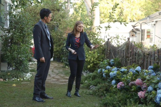 Two characters investigate a garden in front of a house.