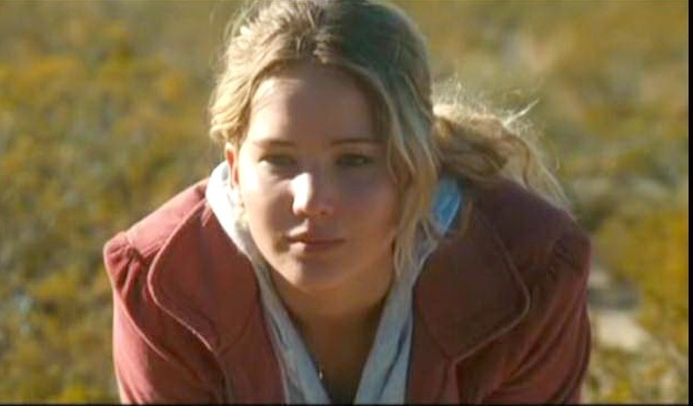 Jennifer Lawrence crouches in a meadow in The Burning Plain