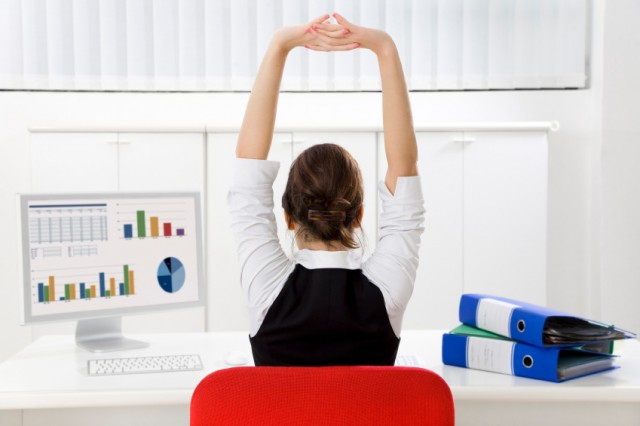 Woman stretching at her desk during work