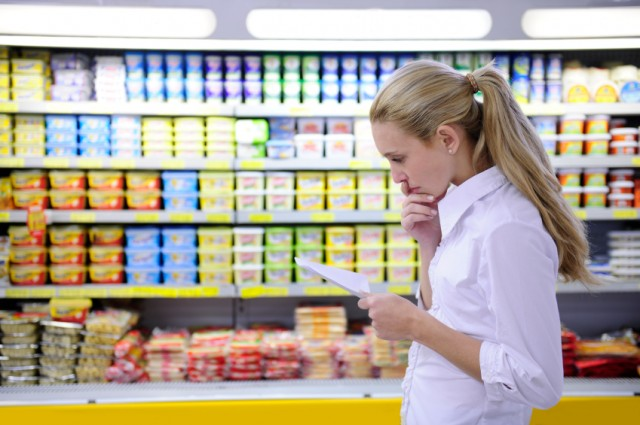 A woman looks at her shopping list as she shops for groceries