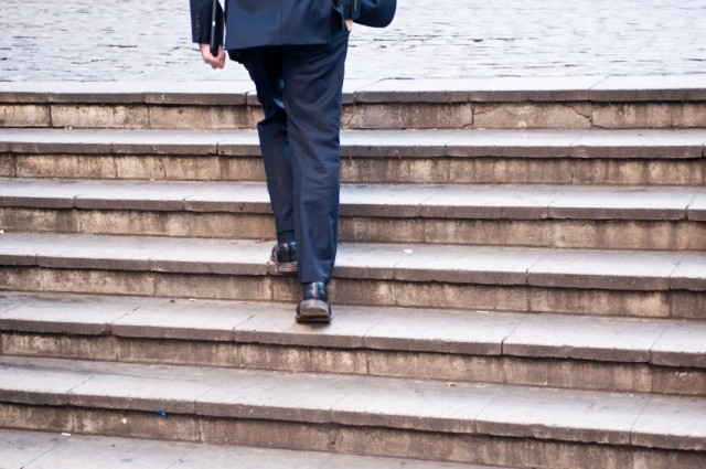 man walking up stairs in a suit