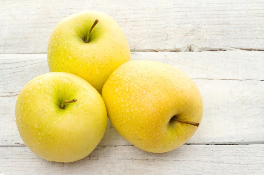 golden delicious apple over white wood