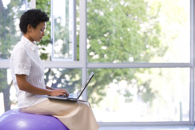 Businesswoman using laptop computer on exercise ball, side view