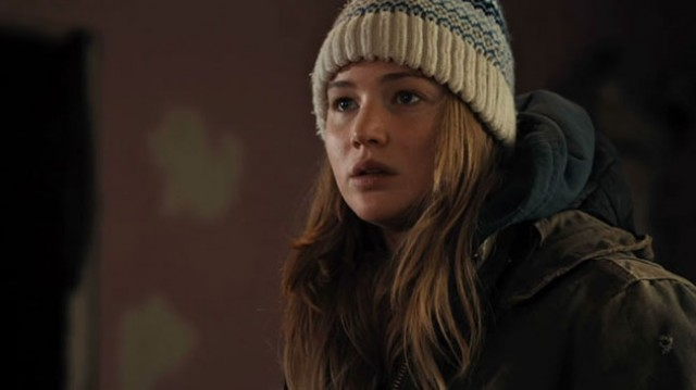 Jennifer Lawrence wears a shocked look on her face while wearing a hat and coat in Winter's Bone