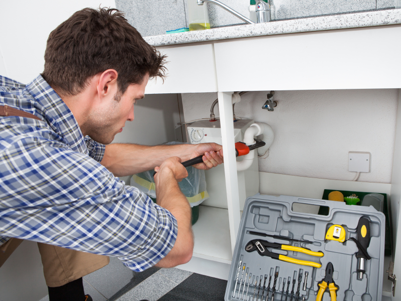 A plumber hard at work on a sink