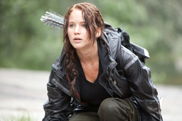 Jennifer Lawrence crouches down in a field while wearing a bow and arrow in The Hunger Games