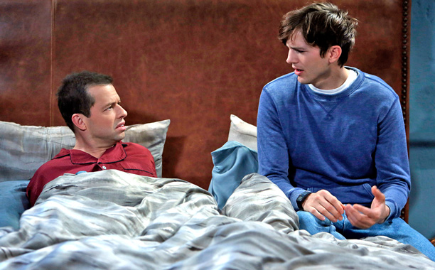 Ashton Kutcher sits next to Jon Cryer in bed in a scene from Two and a Half Men