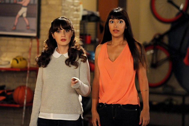 Zooey Deschanel and Hannah Simone stand next to each other and look surprised on New Girl