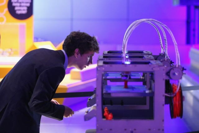 A technician checks on a 3D printer as it constructs a model human figure in the exhibition '3D: printing the future' in the Science Museum on October 8, 2013 in London, England. The exhibition, which opens to the public tomorrow, features over 600 3D printed objects ranging from: replacement organs, artworks, aircraft parts and a handgun. (Photo by Oli Scarff/Getty Images)