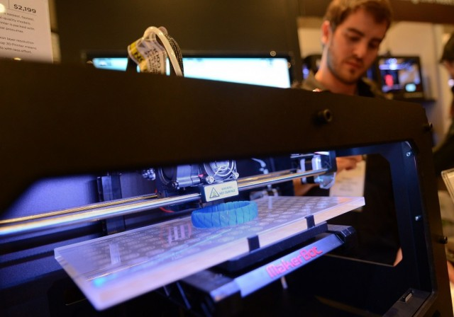Visitors look at a 3D printer printing an object, during 'Inside 3D Printing' conference and exhibition in New York, April 22, 2013. The exhibition features on April 22-23, 2013, tutorials and seminars offering blueprints on how to invest and utilize 3D printing in coming years, as well as leading manufacturers and developers displaying their latest 3D printers and services. AFP PHOTO/Emmanuel Dunand (Photo by Emmanuel Nunand/AFP/Getty Images)