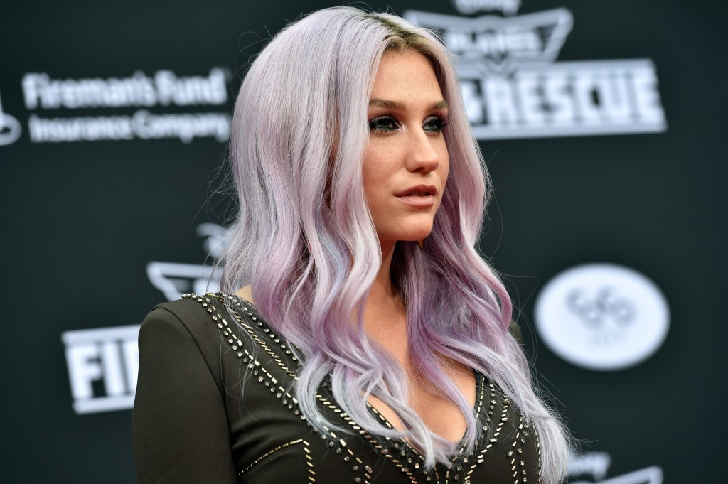 Kesha poses on the red carpet in a black dress and purple hair.
