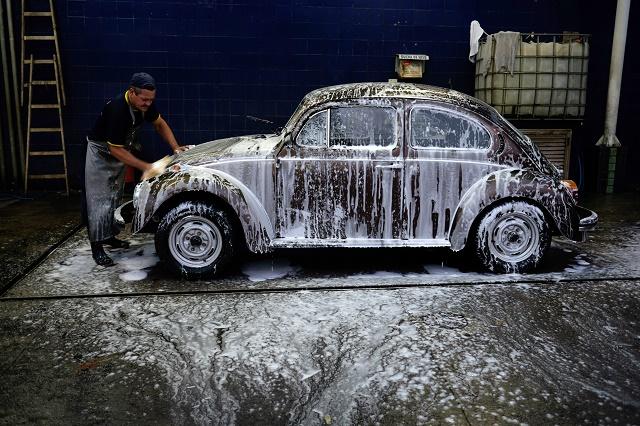 Man washing off an old Volkswagen Beetle