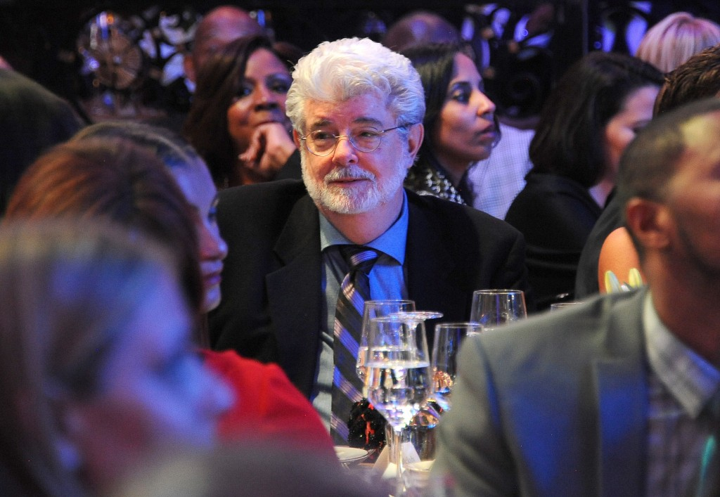 George Lucas at a press dinner, wearing a suit and smiling