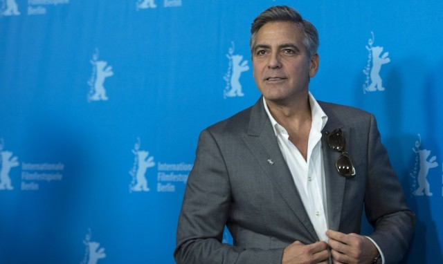 George Clooney adjusts his tux while walking the red carpet
