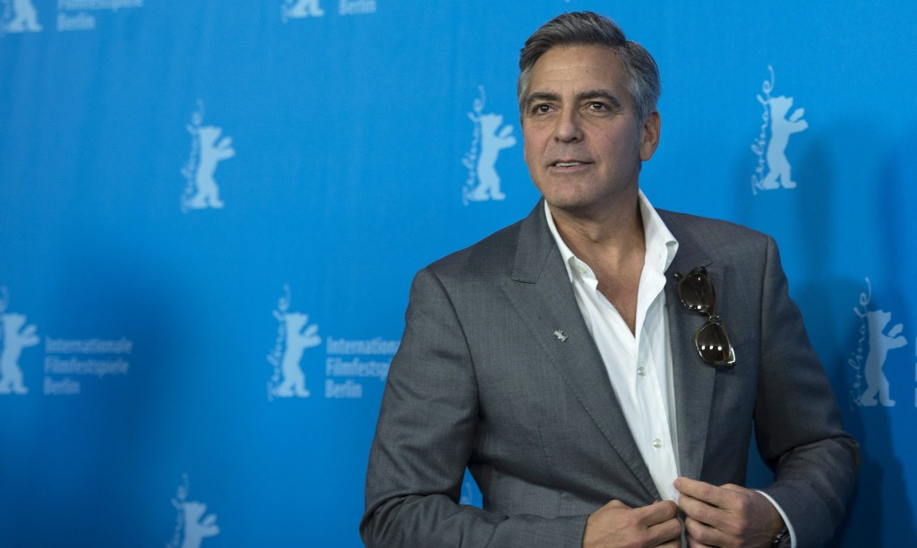 George Clooney adjusting his grey jacket on the red carpet.