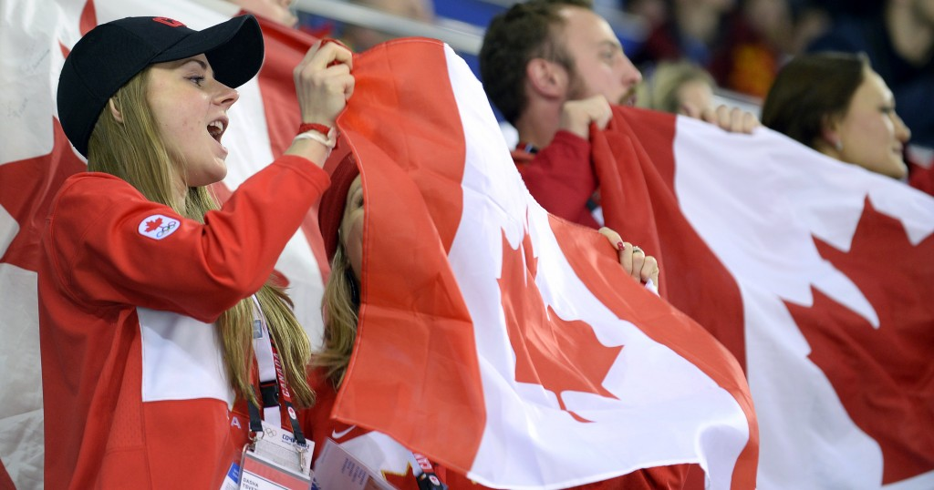 Canada's fans celebrate at the end of the Women's Ice Hockey semifinal match Canada vs Switzerland at the Shayba Arena during the Sochi Winter Olympics on February 17, 2014. Canada won 3-1. (Photo by Alexander Nemenov/AFP/Getty Images)