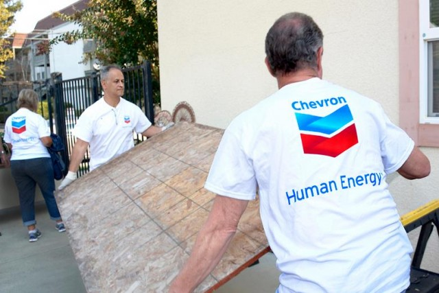 Chevron employees with the company logo on their shirts volunteering.