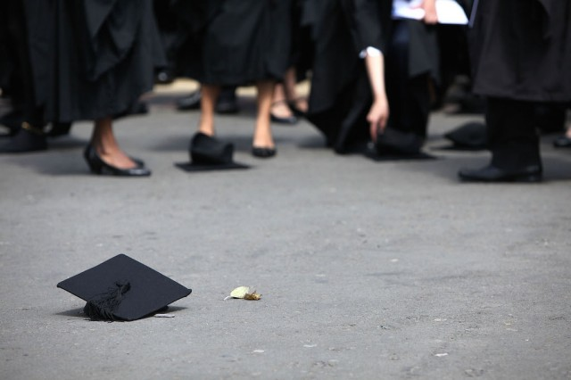 Students pick up their mortarboards after the offical hat throwing photograph at the University of Birmingham on July 14, 2009 in Birmingham, England. Over 5000 graduates will be donning their robes this week to collect their degrees from The University of Birmingham. A recent survey suggested that there are 48 graduates competing for every job. (Photo by Christopher Furlong/Getty Images)