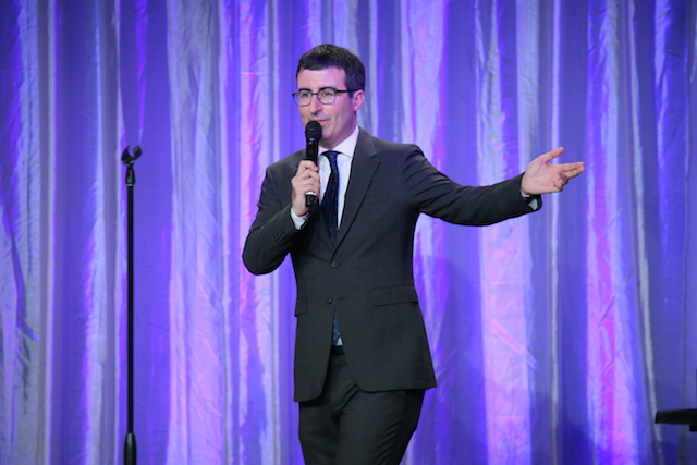 John Oliver speaking into a mic in front of a purple curtain.