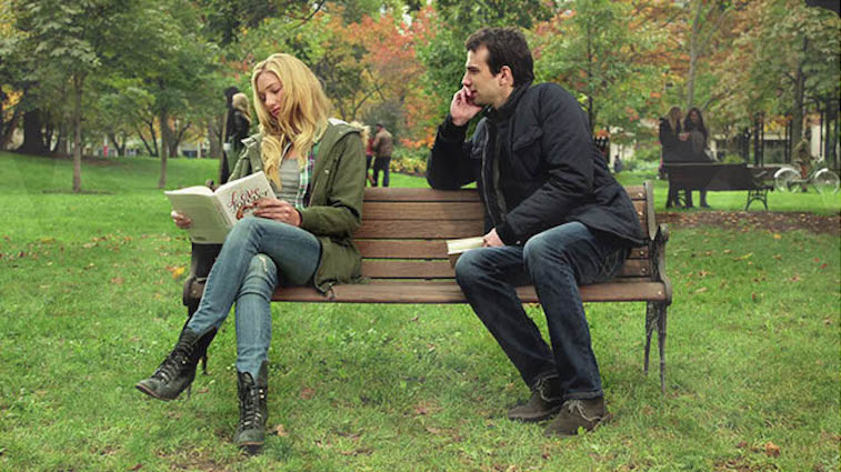 A man sits next to a woman on a park bench