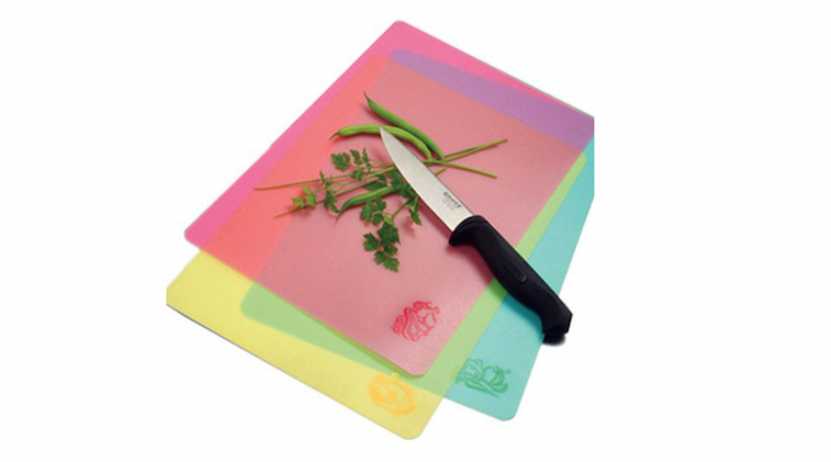 Three plastic cutting boards, a knife, and herbs